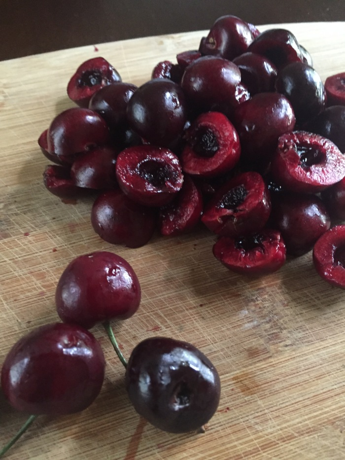 halved and pitted cherries on cutting board