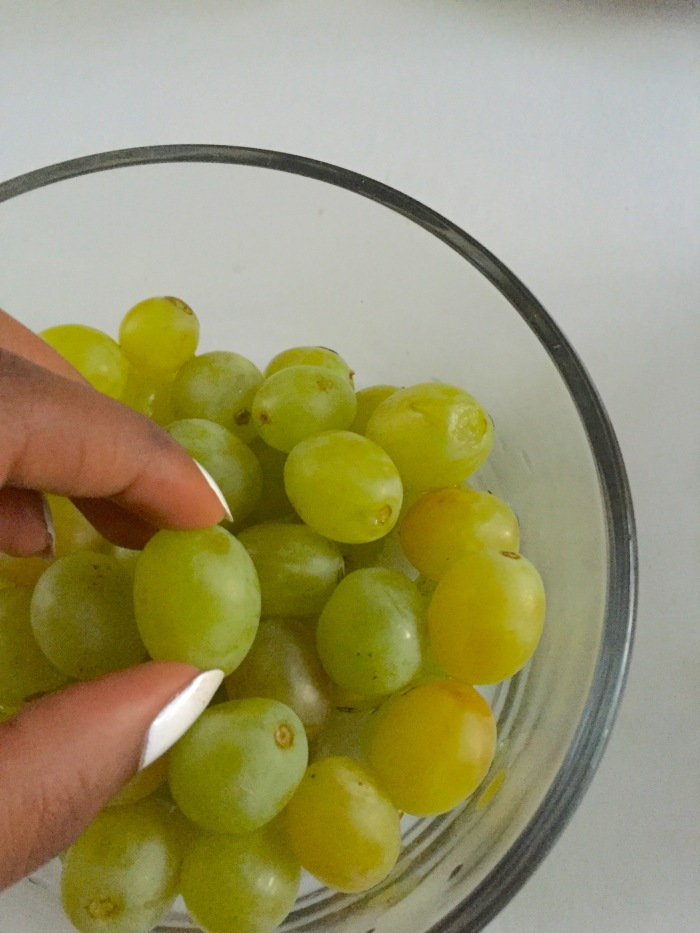 picking green grapes out of bowl