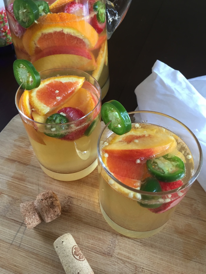A sweet & spicy sangria made with cara cara oranges, jalapeno, strawberries, peaches, sweet white wine, and champagne--perfect for a summer get-together! Recipe by Dash of Jazz